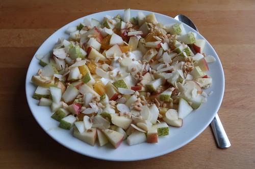 Birne, Apfel, Orange, Mandelblättchen, gehackte Haselnüsse, Honig und Joghurt statt Müsli zum Frühstück