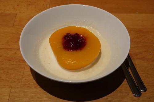 Halber Pfirsich mit Preiselbeeren in Honig-Weinbrand-Schmand-Soße als Nachtisch