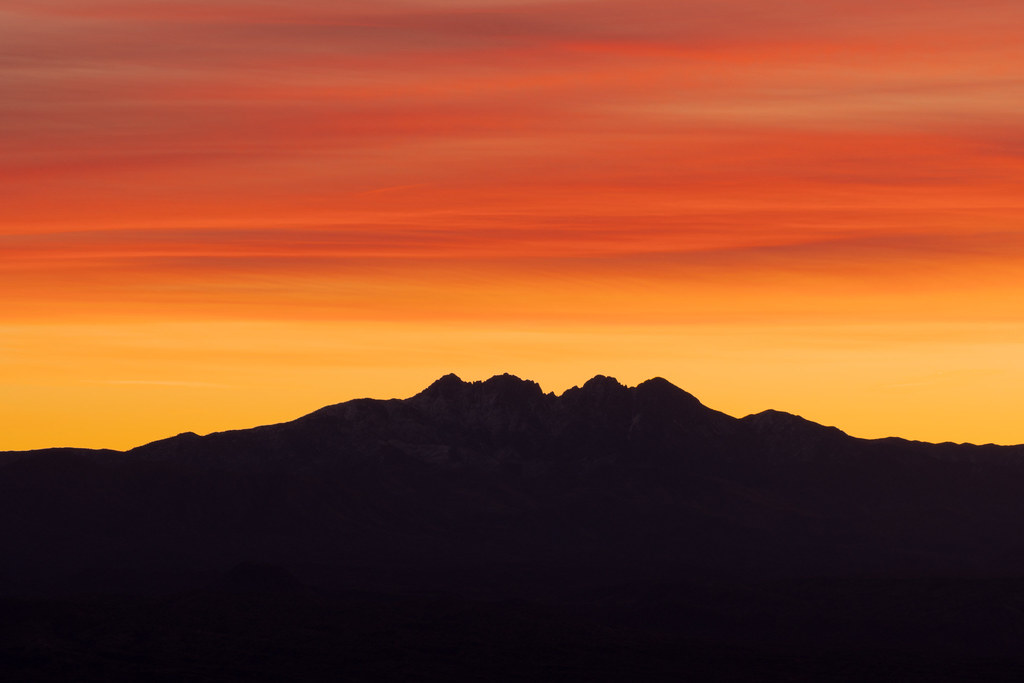 Orange clouds hover above the Four Peaks before sunrise, taken from the Marcus Landslide Trail in McDowell Sonoran Preserve in Scottsdale, Arizona in January 2020