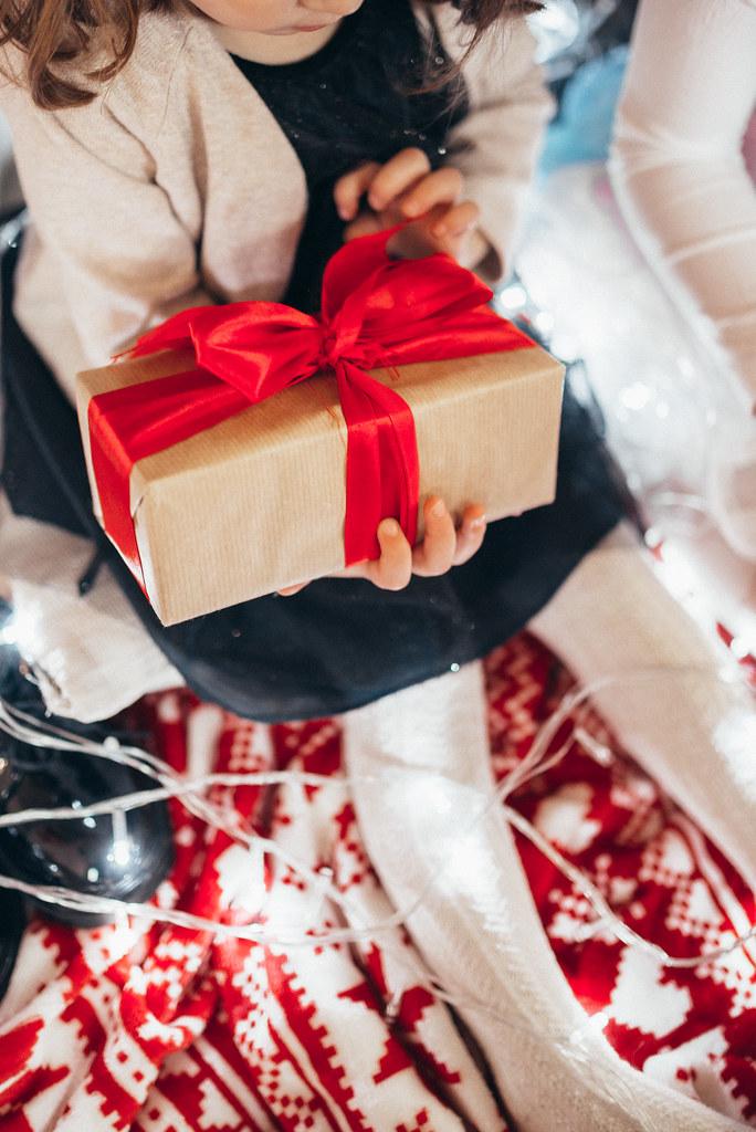 Baby girl holding beautiful Christmas gift. Closeup