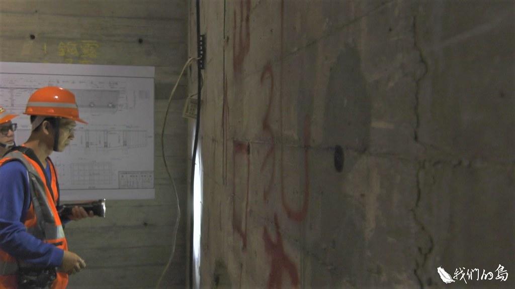 橋檢人員拿著手電筒,沿著牆面仔細檢查,有裂縫就拍照。