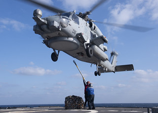 Sailors attach cargo to an MH-60R Sea Hawk helicopter during a replenishment-at-sea. | by Official U.S. Navy Imagery