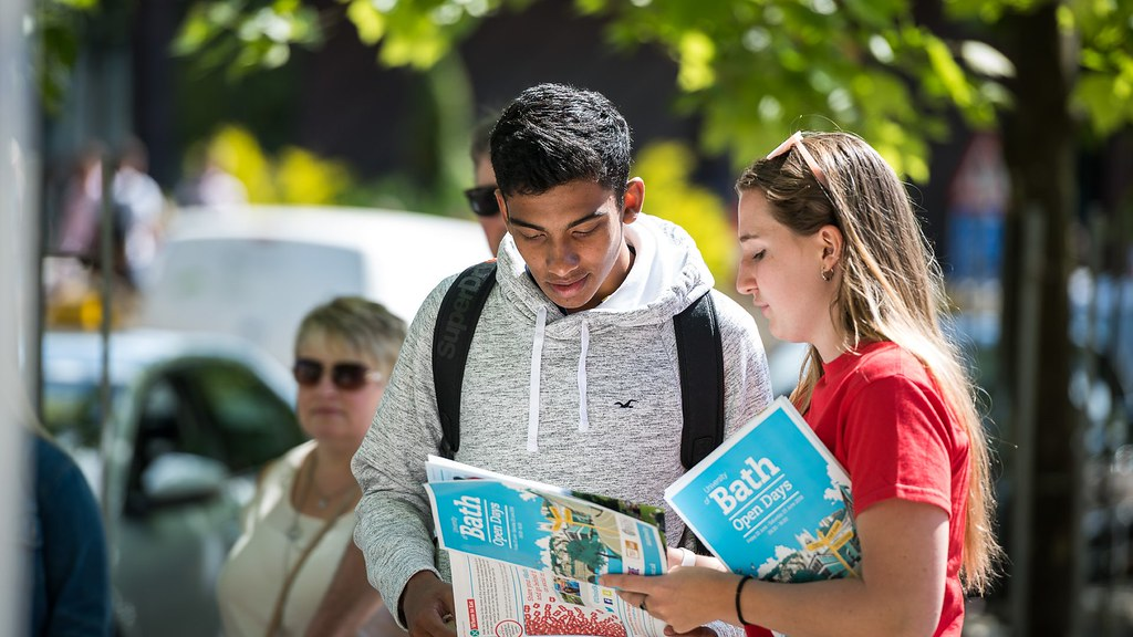 A visitor and a student ambassador looking at the Open Day guide on campus