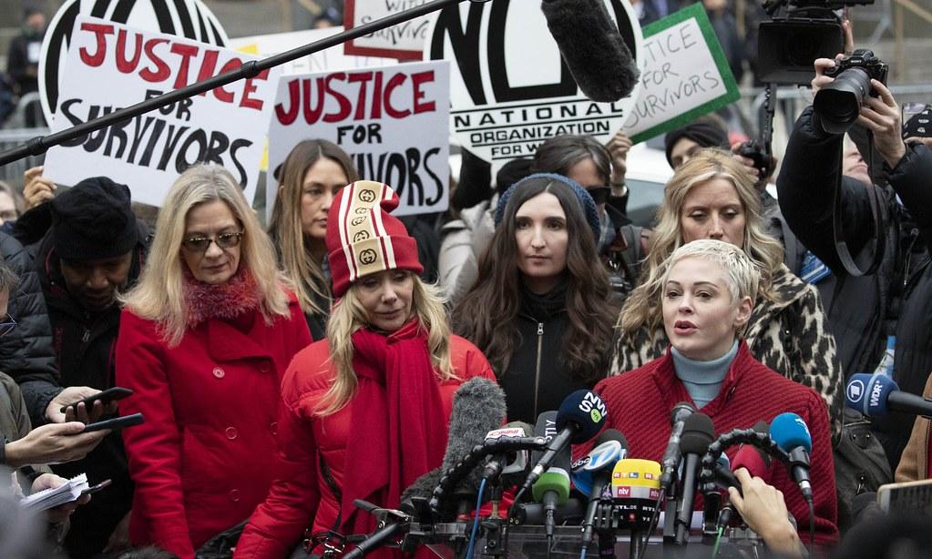 美國演員麥高文與其他性侵指控者於法院外高舉「給倖存者一個公道」標語。(圖片來源: Mark Lennihan/AP)