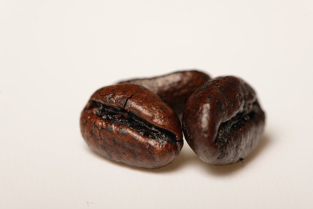 Three coffee beans on the white table