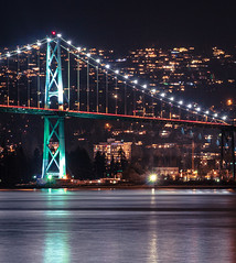 Side view of the Lions Gate Bridge in Vancouver, BC lit up at night.