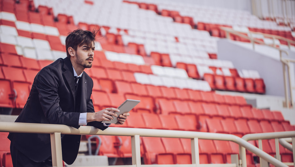 A man dressed smartly standing on the edge of a stadium holding a digital tablet