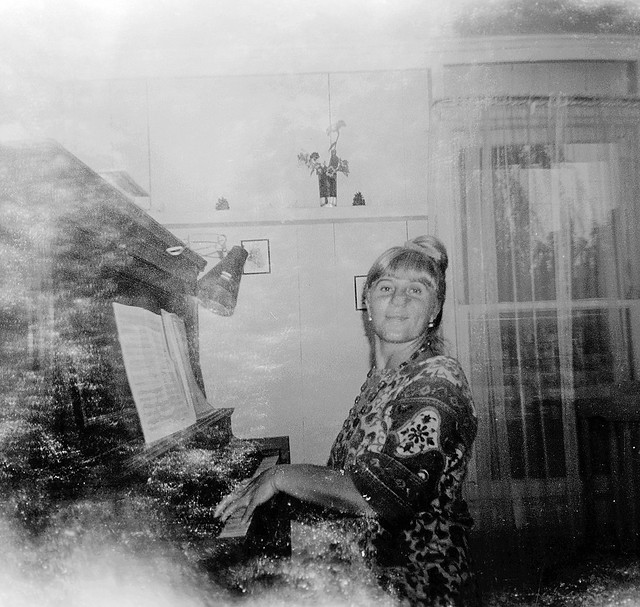 Forgotten film rescue from 1967. Mom at the piano in our living room. Light leaks galore caused by the cheap plastic Diana camera used to take this. A moment in time saved on 120 roll film. Milford, Connecticut. Aug 1967