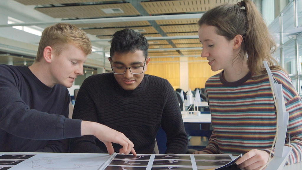 Three students look at their design report in our studio space