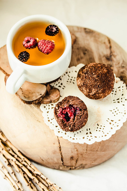 Chocolate balls with fresh berries in the wooden plate on white linen tablecloth backgound. A cup of herbal tea. Kinfolk and comfort food atmosphere concept.