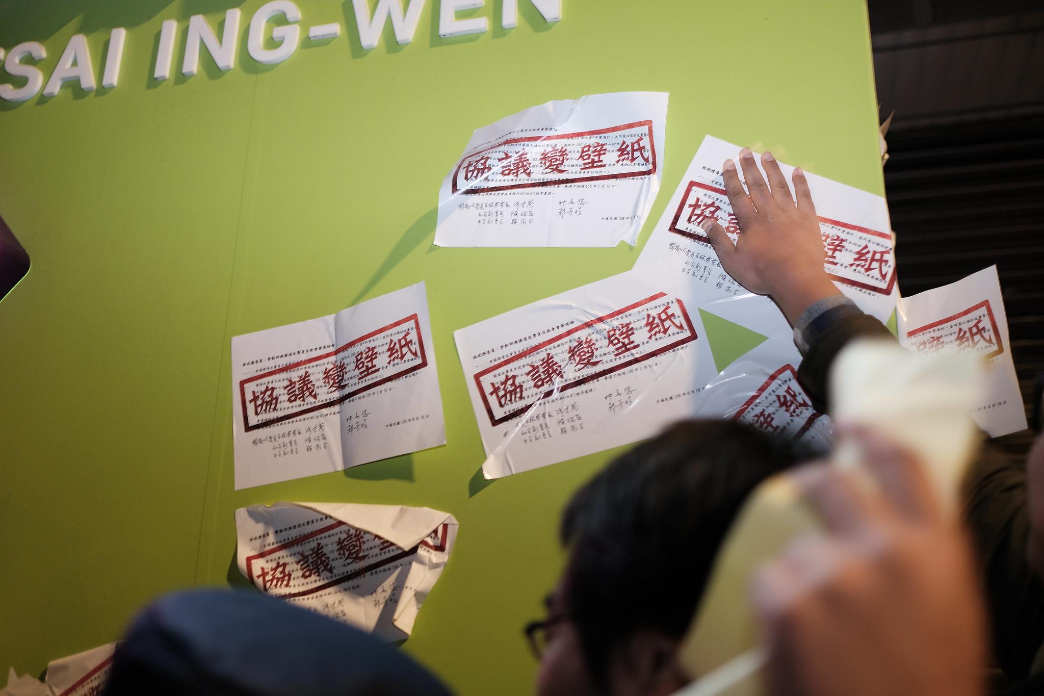 自救會突襲蔡英文競選總部張貼「協議變壁紙」嗆聲貼紙。(攝影:唐佐欣)