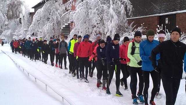 Tåg av löpare på väg till start i snö