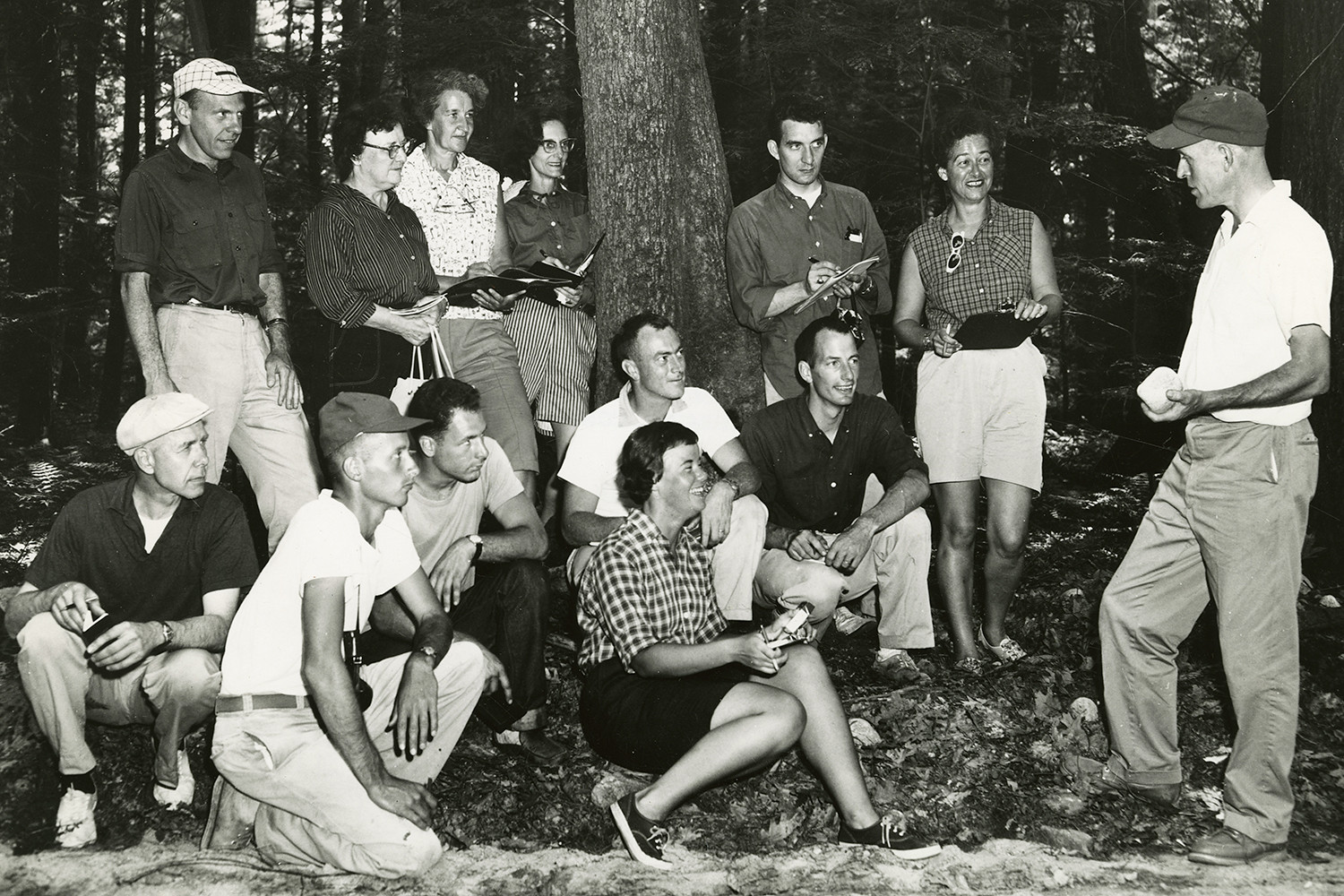A group of people taking notes at a lecture in a forest.
