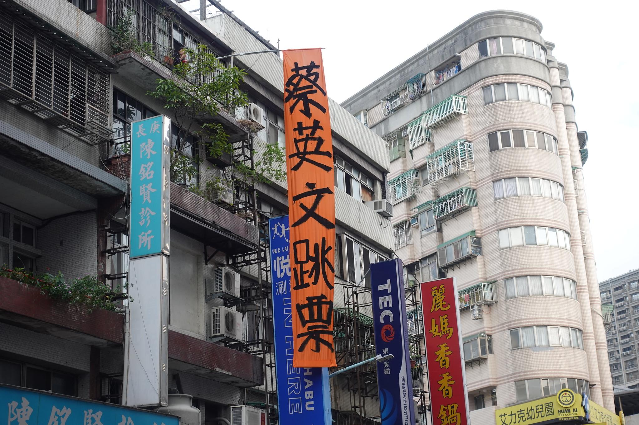 國道收費員自救會從蔡英文掃街沿線公寓頂樓降下「蔡英文跳票」巨大布條。(攝影:張智琦)