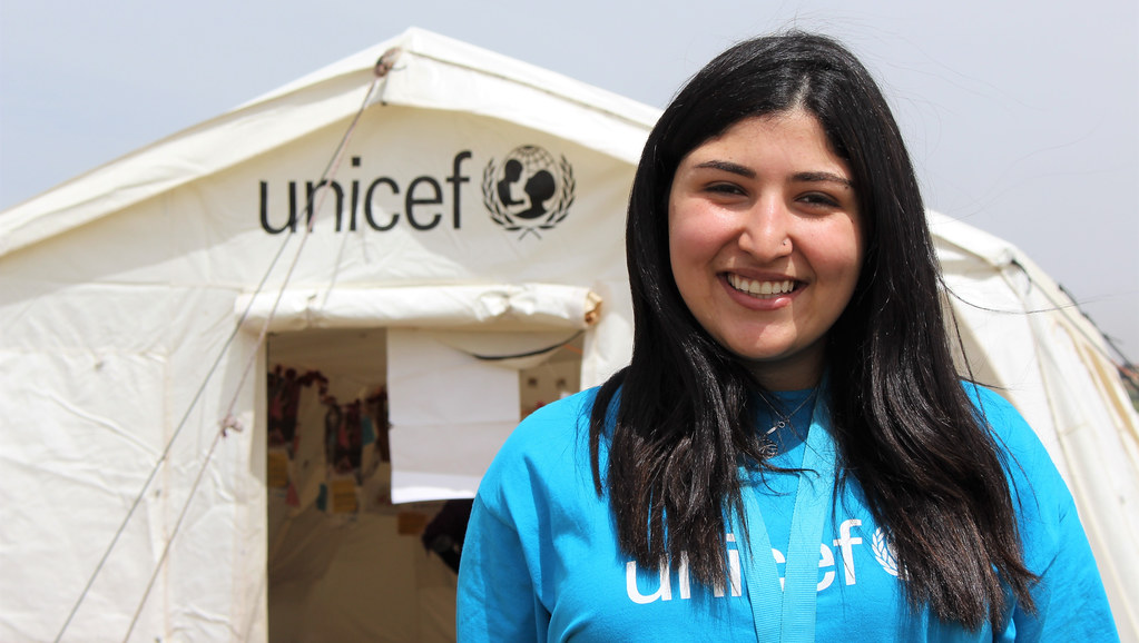 Student Rand Altaher standing in front of UNICEF tent in Jordan