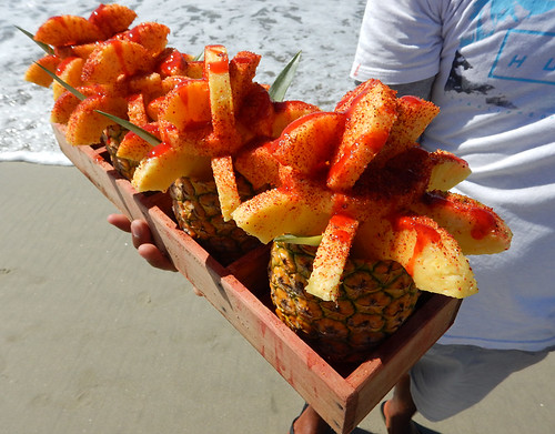 Chamoy drizzled pineapple carried by a beach vendor to tempt customers lounging on the beach in Puerto Escondido, Mexico