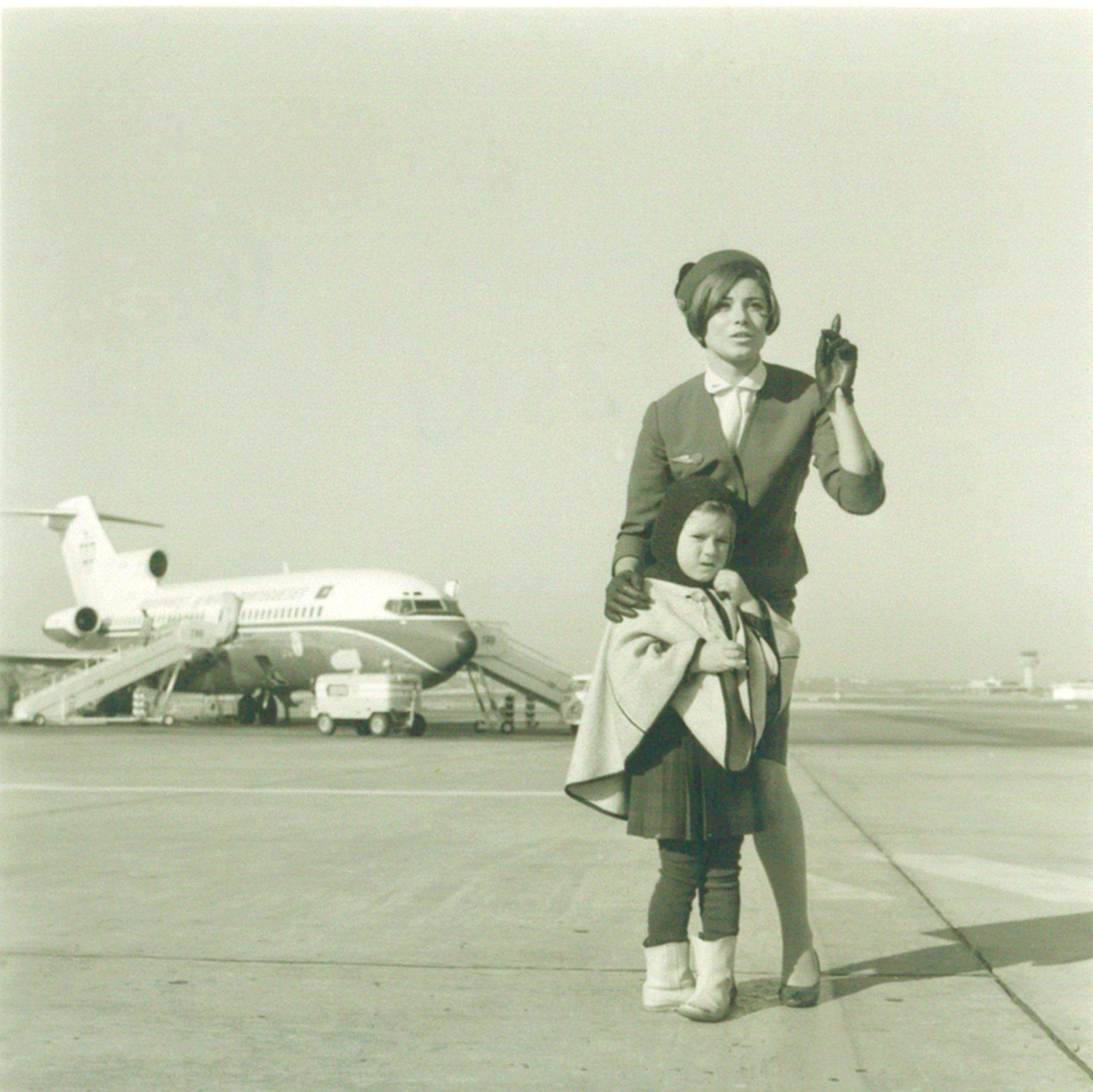 Assistente com 6.º uniforme da T.A.P. e uma menina passageira na pista da Portela; ao fundo do Boeing 727, Lisboa [?], 1968.