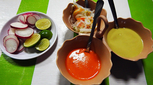 Taco accompaniments of radishes, limes, pickled vegetable, red hot sauce and even hotter green salsa made with the green ghost chiles, at a Tacos Pastor place in Marquelia, Mexico