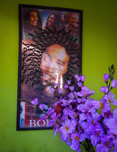 The hairdressers were having fun with this Bob Marley poster set on an improbably green wall with purple bouquet in front in Tecoman, Mexico