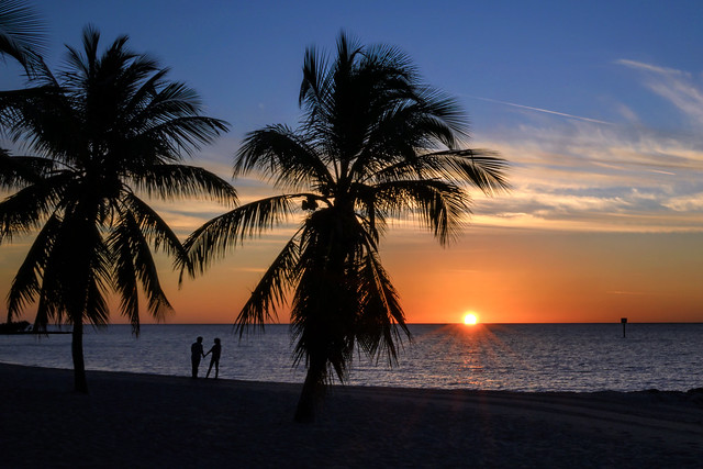 Couple in silhouette at sunrise on Smathers Beach, Key West, Florida