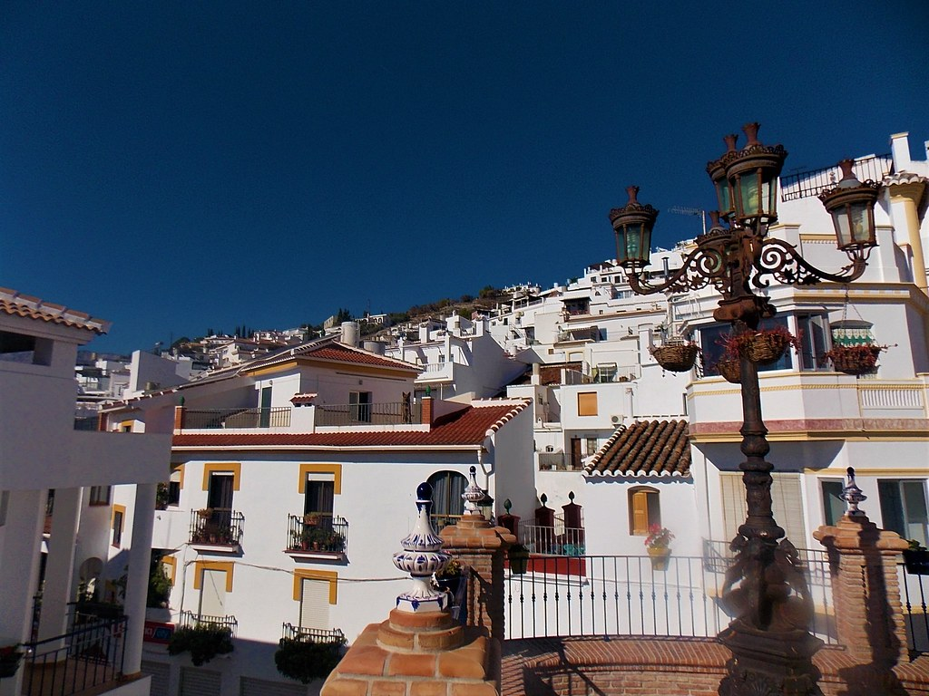 White houses with yellow window seels spreading up the hill. In front there is a lamp post with 4 arms from which baskets with pink flowers hang.