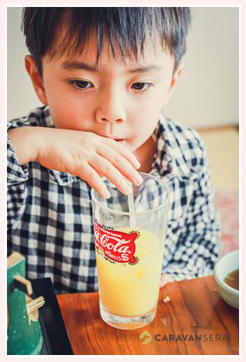 ストローでオレンジジュースを飲む少年