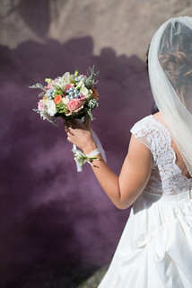 A close up of a bride's hand and her bouquet with purple smoke | by shixart1985