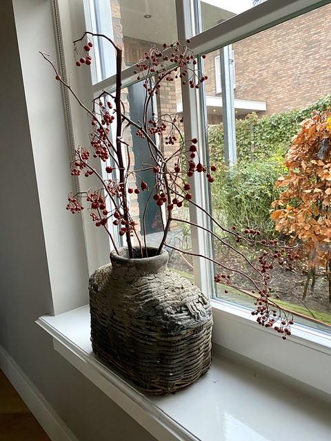 Leemkruik met rozenbottel in de vensterbank