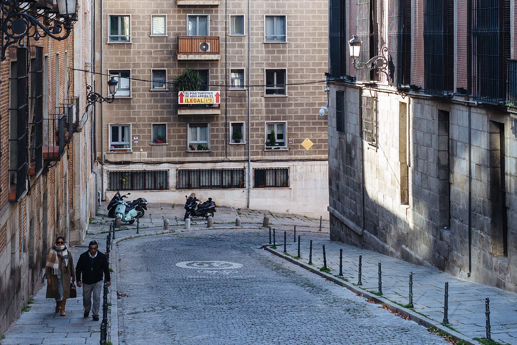 Two people bundled up in coats and scarves walk uphill in the shade along a narrow street in central Madrid. An apartment balcony bears a large poster pointing to the apartment above.
