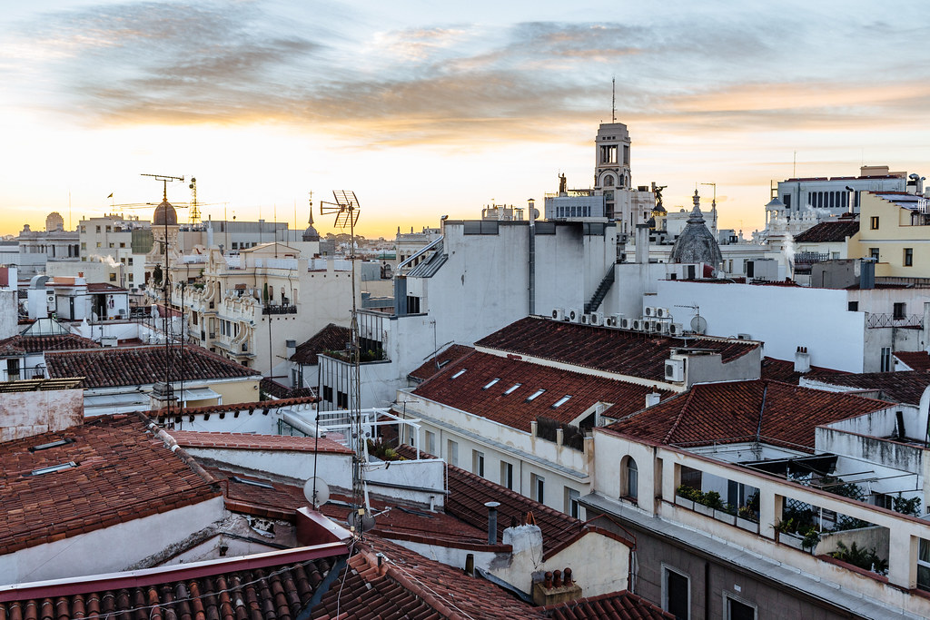 Clay tile shingles and rooftop patios of buildings in central Madrid