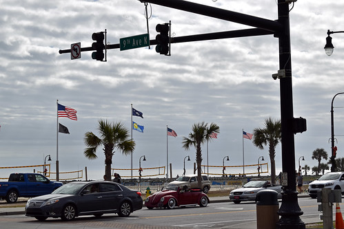 myrtlebeach sc southcarolina horrycounty outdoor outside outdoors intersection trafficlight redlight flag flags volleyball volleyballnets beachvolleyball ocean atlanticocean water bodyofwater vehicles traffic pavement paved street clouds cloudy overcast greysky sky graysky palmtree palmtrees palm tree trees greenery foliage americanflag usaflag usflag unitedstatesflag weekend december saturday afternoon saturdayafternoon beach travel tourism nikon d3500 dslr toyota blue ford fordstxpickup convertible vw volkswagen chrysler pole utilitypole streetsign chevy hhr chevrolet