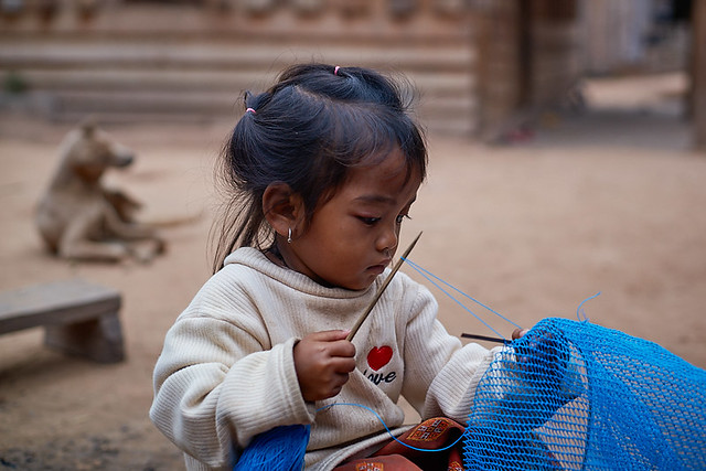 Laotian little girl sewing 1