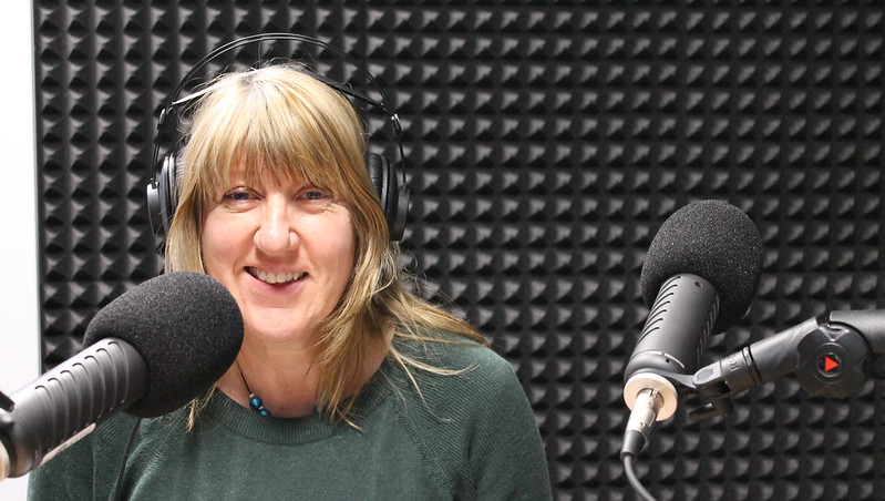 Rachel Forrester-Jones sits in front of a microphone to record a podcast