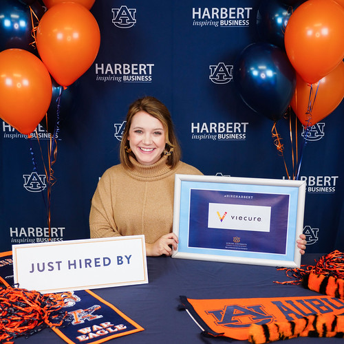 Megan Thompson sits at a table decorated in blue and orange.