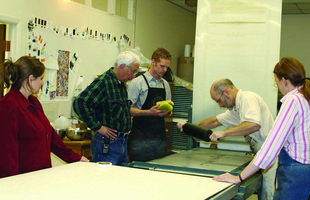 Richard Finch rolling up a lithography plate