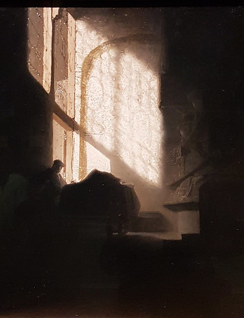 A Man seated reading at a Table in a Lofty Room by a follower of Rembrandt