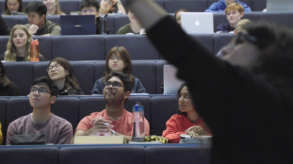 A female lecturer directs her class's gaze to the screen behind her