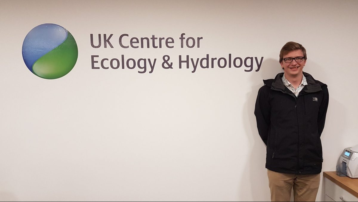 Andy Barnes stands in front of UK Centre for Ecology & Hydrology logo on a wall.