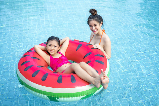 Asian mother play with her daughter in a swimming pool in a tropical resort,