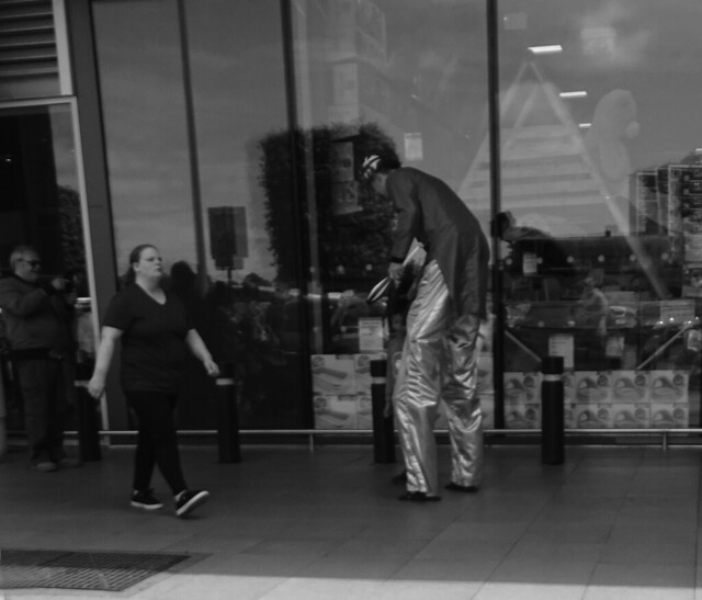 BLACK AND WHITE PHOTO OF A STREET ENTERTAINER OUTSIDE A SHOP OR STORE WITH PEOPLE WALKING PAST IN AN EAST LONDON BOROUGH SUBURB STREET ENGLAND  DSC02152