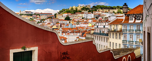 lisbon portugal street sunny afternoon sky blue serene quiet houses roofs view perspective facade window downhill hill slope typical picturesque castle historical graffiti