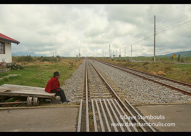 Indigenous highlander waiting for a train, Urbina, Ecuador