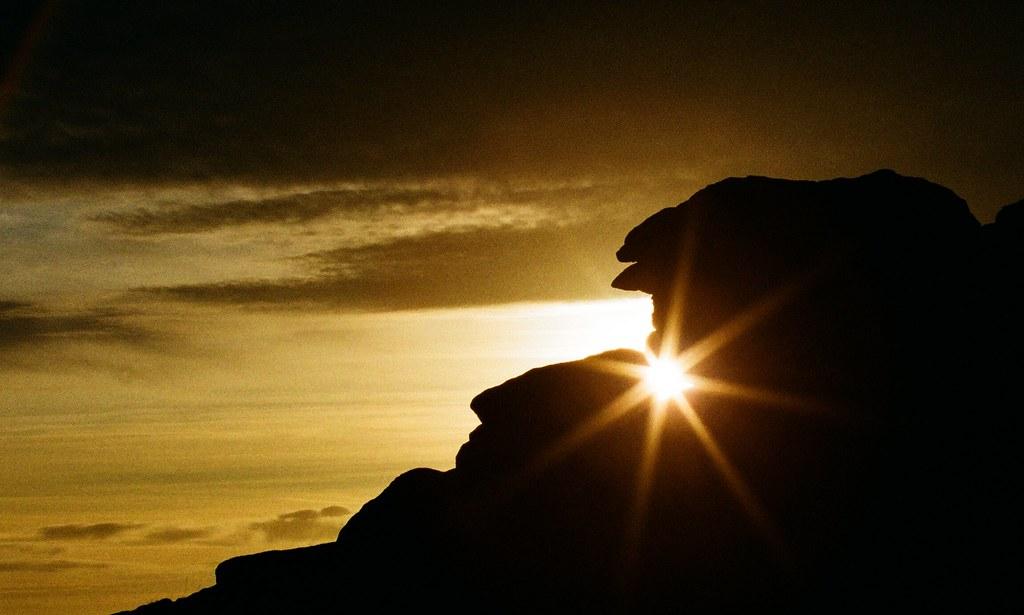 Hidden sunset creeping through a gap in the rock on Dartmoor