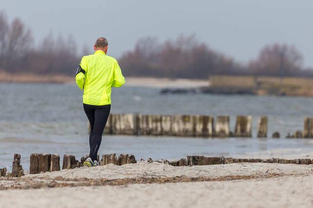 Mann with reflecting yellow sports jacket running on a beach near Beach Resort Makkum