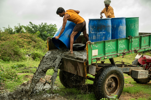 (L-R) Muniraju, 37, and Krishnappa, 65, pour out the contents from emptying the pit in Bengaluru, India. August 2019.  Source: WaterAid/ CS Sharada Prasad/.