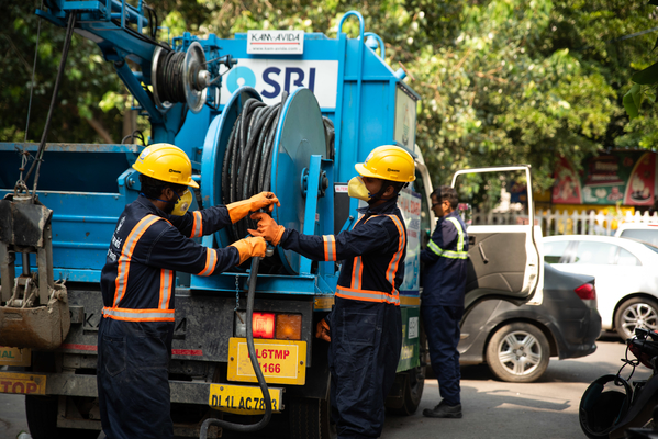 Sanitation workers use a 120 foot long jetting hose connected to a mechanised truck to service sewers on streets of Delhi, India. 2019 Credit: WaterAid/ CS Sharada Prasad