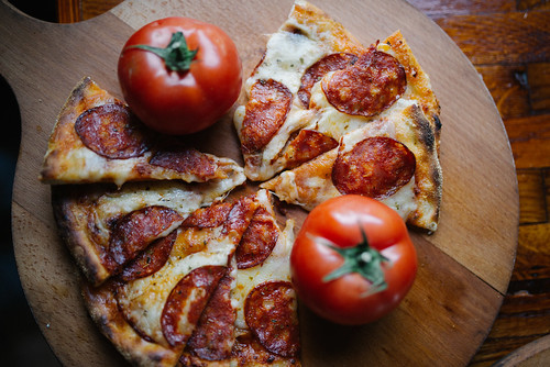 Multiple slices of pizza served on a wooden plate with tomato