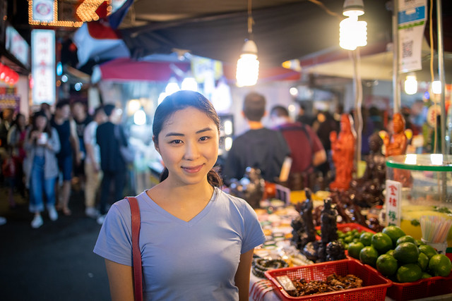 Portrait of young woman in night market