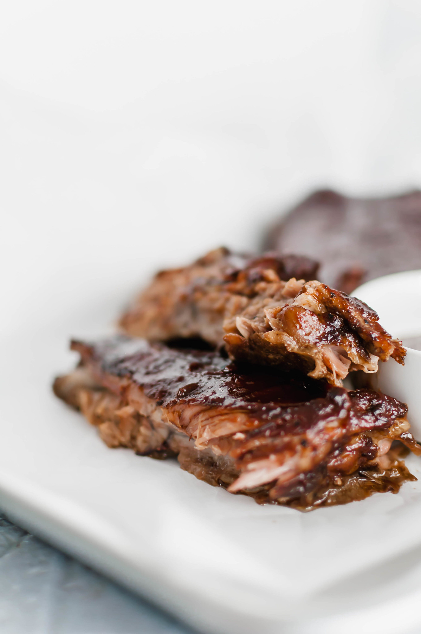 These Oven Baked Ribs are the ultimate in comfort. So simple and unbelievably tender. Rubbed with a delicious, rich coffee rub, baked then slathered in bbq sauce.