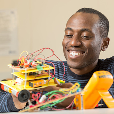 A student smiles as he examines his electric racing robot